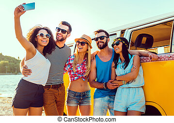 Capturing summer fun. Group of happy young people bonding to each other and making selfie while standing near their retro mini van