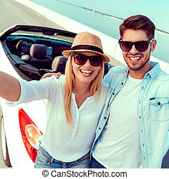 Capturing the bright moments. Top view of cheerful young couple making selfie while standing near their white convertible