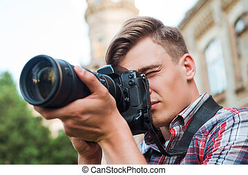 Capturing the moment. Handsome young man taking a photograph with his digital camera while standing outdoors