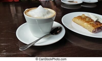 Capuccino and pancake with sour cream on the table in cafe...