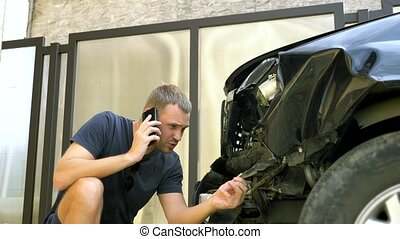 car accident concept. man in a state of shock talking on the phone after a car accident, standing by a car with a broken bumper.