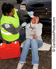 Car accident - Female paramedic attending to a young car...