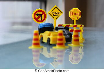 car Accident zone cordoned off with a yellow stop sign post. two cars with a major collision with one car toppled by another brown car & area cordoned by yellow barricades