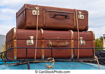 Car and luggage - Hand carryon on the roof of retro car tied...