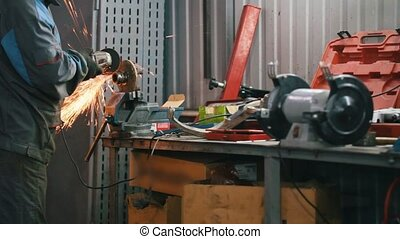 Car auto service - worker grinding metal construction with a circular saw