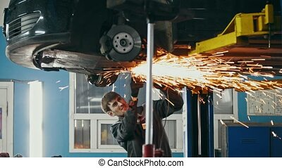 Car auto service - worker grinding metal construction with a circular saw under bottom of the vehicle