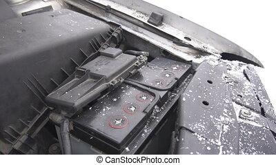 Car battery in winter in frost, it is snowing, weak battery,...