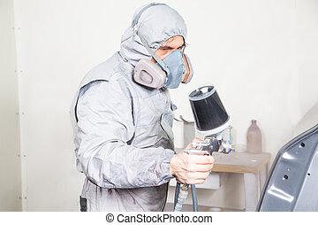 Car body painter spraying paint on bodywork parts - Car body...