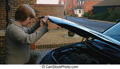 car bonnet - woman lowering the bonnet, hood, of the car