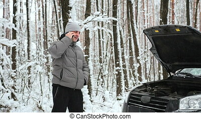 Car broken down on a snowy road in the forest. - The driver...