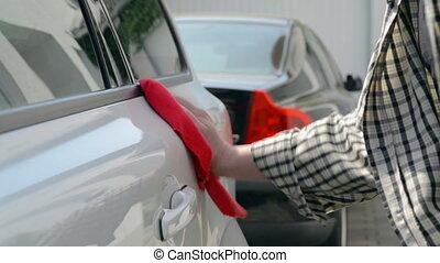 Car Care - Woman polishing a white car with a red polishing...