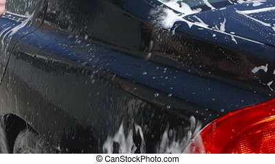Car Care - Man washing a car by hand using a sponge and a...
