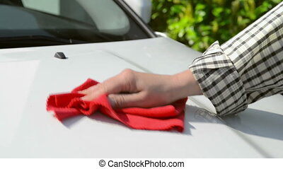 Car Care - Woman polishing a white car with a red polishing...