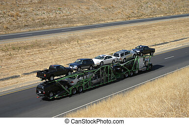 Car Carrier - A large truck delivers new cars via highway.