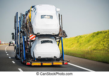 Car Carrier Trailer Full of Vehicles Driving Down the Highway
