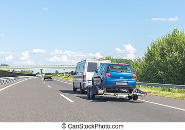 Car carrier trailer with blue car on highway