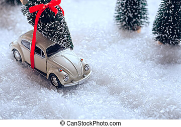 Car carrying a Christmas tree in snow covered miniature evergreen forest