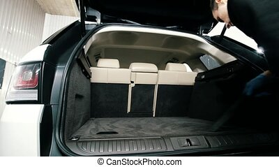 Car cleaning - man cleans wardrobe trunk of luxury vehicle with a vacuum cleaner