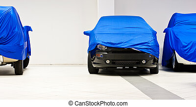 Car covered by a blue sheet in a dealership