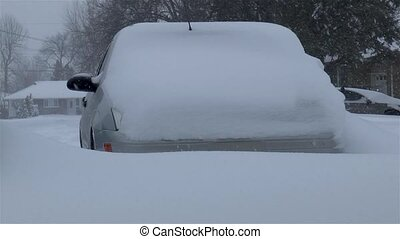Car covered by snow, under severe winter storm.