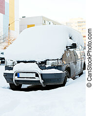 Car covered with snow on the street in winter.