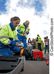 Car crash scene - Paramedics tending to the first aid of an...