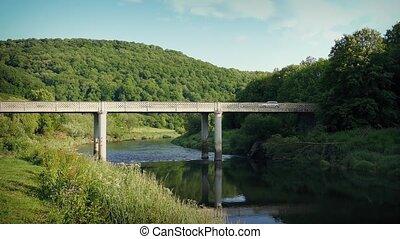 Car Crosses Bridge Over River