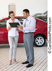 car dealer explaining sales contract to young woman