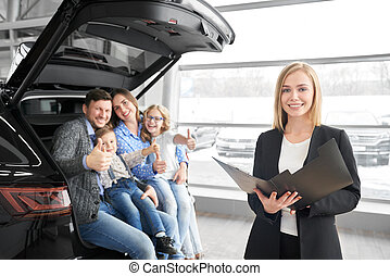 Car dealer posing at camera with family, buyers of new car.
