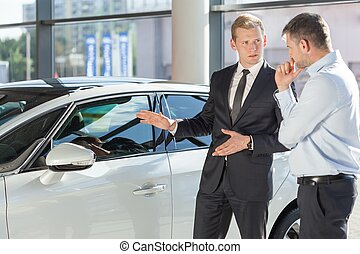 Car dealer showing vehicle to mature man