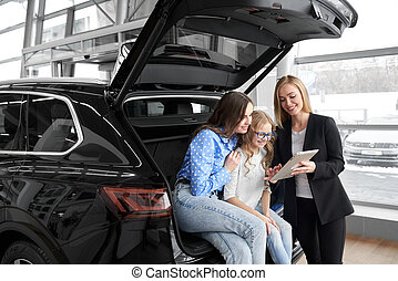 Car dealer working with clients in dealership.