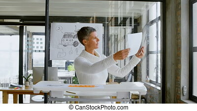 Car designer checking car sketch design in office 4k -...