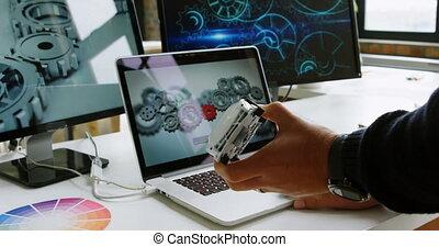 Car designer using laptop at desk in office 4k - Close-up of...