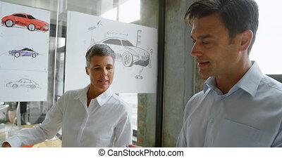 Car designers discussing on model car 4k - Car designers...
