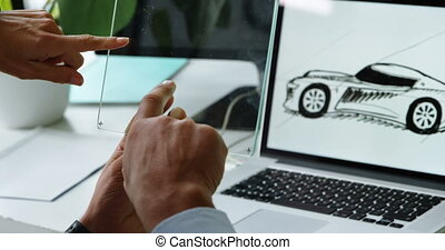 Car designers discussing over glass digital tablet in office...