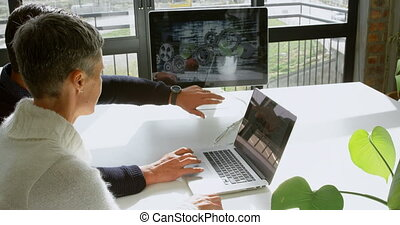 Car designers discussing over laptop at desk 4k - Car...