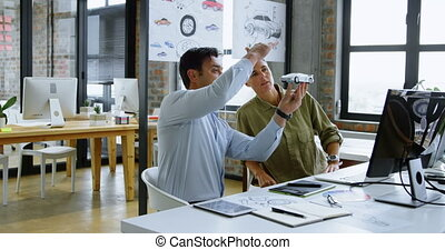 Car designers discussing over model car at desk 4k - Car...