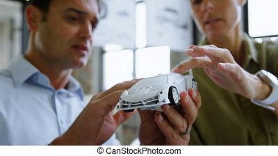 Car designers discussing over model car at desk 4k - Car...