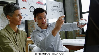Car designers discussing over model car at desk 4k