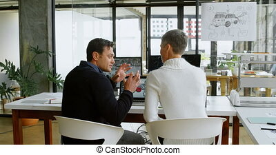 Car designers discussing to each other at desk 4k - Car...