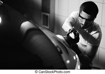 Car detailing - man with orbital polisher in auto repair ...