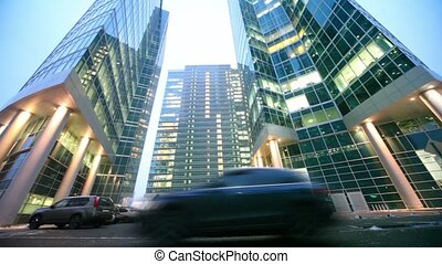 Car drive by road in front of three skyscrapers