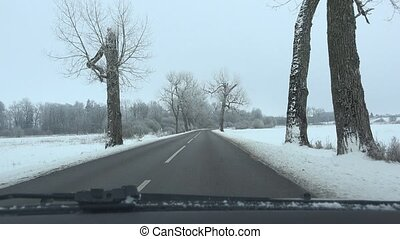 car drive on icy winter road and frosted trees alley. 4K -...