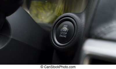 Car driver pressing a button and starting the engine