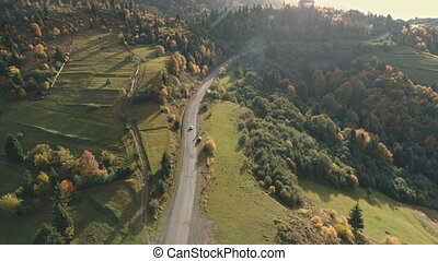 car drives along grey winding asphalt hilly road running to camp among mixed dense forests and green meadows aerial view. Carpathian mountains, Ukraine beauty nature. Travel, wild recreation. 4K
