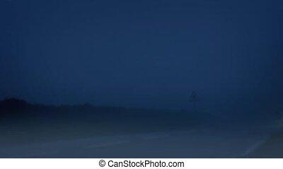 Car Drives On Foggy Road At Night