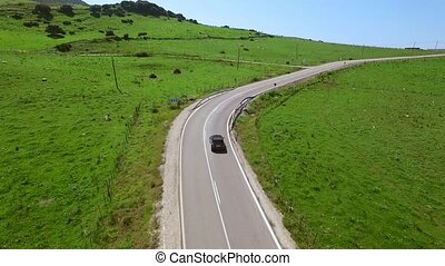 Car driving along a winding rural road