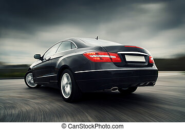 Rear view of black luxury coupe driving fast