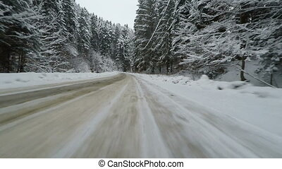 Car driving in a beautiful winter forest, snowy Christmas...