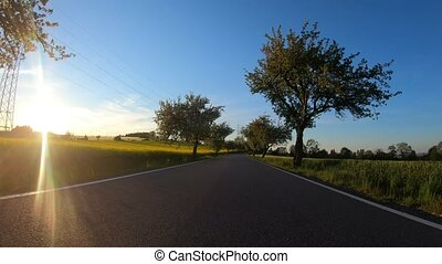 car drive in spring countryside road, sunny landscape with field and meadow. Europe travel concept
